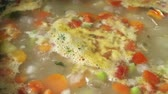 cocinando : A closeup of a boiling soup, looking delicious.