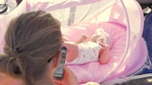 outing : Woman browsing social network on cell phone being outdoor with baby daughter lying in pink portable bassinet