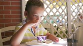 icecream : Slow motion shot of a boy enjoying sweet chocolate ice-cream in cafe on summer day