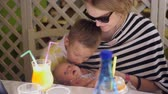 idősek : Mother with two children in cafe. Woman and her elder son kissing baby by turn. They love little daughter and sister