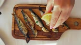 アントレ : Close-up shot of a woman pouring grilled sardines with lemon juice. Fish served on wooden board 動画素材
