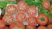 купец : Greengrocer counter with fresh ripe tomatoes being cut for buyers to see
