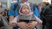 kanguru : Mother carrying baby daughter in kangaroo carrier. They waiting at the airport. Woman kissing lovely quiet child in knitted pink hoodie onesie Stok Video