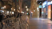 bisiklete binme : Steadicam shot of walking in night city street illuminated with banners and passing by bike share station. Valencia, Spain Stok Video