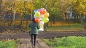 daytime : A slowmotion of a woman walking with colorful balloons in a hand.