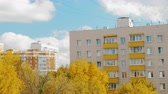 blok mieszkalny : Autumn scene of the city with apartment houses, yellow trees and blue sky with white clouds Wideo