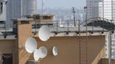 broadband : Brick house rooftop with several satellite dishes, city view in background
