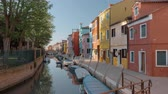 Burano island scene. Italy. Perspective view of coloured house alongside the canal with moored boats. Unidentified people walking in the street