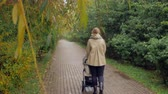 dlažba : Back view of a mother with baby carriage outside. Woman with pram walking in the park on rainy autumn day