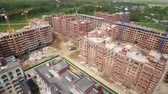 Aerial shot of apartment complex under construction and new built blocks of flats in New Moscow area, Russia. Spring view
