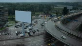 los : Timelapse shot of car traffic on multilevel crossing. City view with hotel, parking lot and blank banner on rainy day