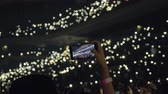 flashlight : Woman taking mobile video of crowded concert hall. People with lights in the darkness