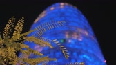 nowoczesny budynek : Low angle shot of modern highrise building Torre Agbar tower illuminated with blue light and blinking at night, tree branch in foreground. Shot with changing focus. Barcelona, Spain Wideo