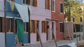 authentique : Colorful residential facades of italian Burano. Small houses are blue, pink, yellow, white and red. Window shutters are opened and bed linen is slowly swaying in the wind. Green tree branches are seen between the houses and warm sunrays are coloring brigh