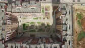 plac budowy : A top view of a multi storey residential building complex with a green lawn in the middle of it. It is surrounded by construction sites and parked cars Wideo
