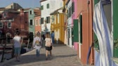舗装された : A blurred scenery of italian Burano with walking tourists. Colorful facades of small houses against the blue sky. Warm sunrays on a paved embankment. People in summer clothes are slowly walking along