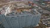 moszkva : An aerial view of a multi storey residential building construction on a bright sunny day. A construction crane is located close to the building. There is a large urban scenery on the background with busy roads, parking lots, residential and industrial bui Stock mozgókép