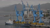 haulage : Industrial port with container cranes and moored cargo ship, distant coastal city and mountains in background Stock Footage