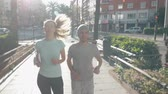 フロント : A young sporty couple finishes tying shoes and start running through a central Valencia street, we see them from the front 動画素材