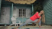 estendido : Mature woman is having a yoga training near the blue bungalow on sandy beach. Blond lady is standing on mat in extended side angle pose and turining to high lunge while doing exercises for her spiritual and physical health.