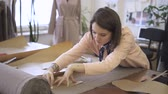 marcado : Young female tailor is making markings on tissue with chalk, standing at table in sewing studio, fashion designer is in working process with fabric at desk, dummy in dress in bright room. Concept: workplace, woman dressmaker, create garment. Stock Footage
