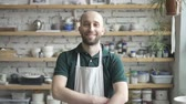 handiwork : Portrait of male ceramist, who is standing in his studio and watching to the camera, slow motion. Young man in green polo t-shirt and white dickey has beard and smiling. Wooden shelves with colours, tools, dishes and plants are on the backgound.