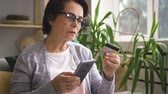magasin vetement : Elderly woman is shopping in online store, using phone and bank card, female is paying for purchases with credit card, holding smartphone in hand, sitting in home interior. Concept: internet banking, electronic systems, buying.