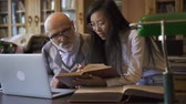 profesor : Female asian research assistant showing the book page to mature male professor working on laptop in the library. Indoors.