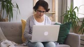 surfista : Senior woman in glasses and grey cardigan writing a text on her brand-new laptop sitting on the sofa in her cozy home. Indoors. Portrait.