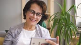 retirement home : Mature woman in glasses, with brown hair having video call on her smartphone, smiling and waving hand sitting on sofa at home. Indoors. Portrait.