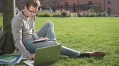 egyetemi : Very cute and pretty guy is sitting in the park and working with computer. Man is so attentive and serious looks through the tablet and note all important information in notebook that you want to join him at this sunny wonderful day.