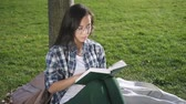 格好の良い : Front view of asian american woman reading book, sitting outdoors. Female student in eyewear having enjoying time, relaxed in good mood. 20s person is in education process. Concept: lifestyle shot, mi