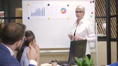 rotafolio : Female entrepreneur presenting financial stratey to multiracial colleagues. Businesswoman standing near whiteboard on briefing. Archivo de Video