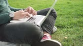 mobility : Close up hands of african college student surfing internet sitting on grass. Young man using laptop computer for browsing, communication and studying. Stock Footage