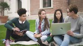 collaborating : Medium shot of adult multiethnic american friends man and woman group using laptop technology coloborating and programming academic project on university campus. Multiracial group of mixed race student hanging out near school buildings together Stock Footage