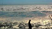 cutting fish : silhouette people walk on beach when sunset and ebb tide
