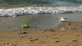 ervas daninhas : plastic cup and waste on the beach and the waves blew them into the sea Stock Footage