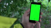 tenso : Closeup of male hands holding smartphone with green screen-prekeyed effects.nature in the background.