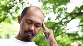 ifade : Adult asian man having a headache in the park