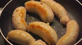almanca : delicious fried pork sausages in a pan in oil close-up