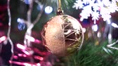 kerstbal : big transparent christmas tree ball full of golden tinsel spins among green branches close view
