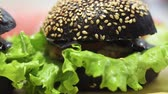 ハンバーガー : black burgers with cutlet cheese and salad close-up. selective focus 動画素材
