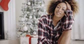 young : Happy young woman in front of a Christmas tree Stock Footage