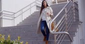 moda : Stylish woman walking down a flight of stairs