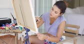 patio : Attractive female artist working on a canvas Stock Footage