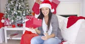 holiday : Curious young woman shaking a Christmas gift