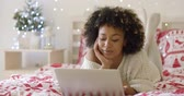 conversation : Beautiful woman in bed laughing at computer Stock Footage