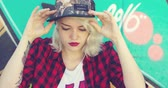 perfurante : Beautiful young hipster blond woman wearing a baseball cap with a pierced lower lip sitting in front of colorful graffiti looking to the side with a serious expression.