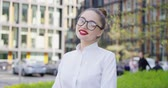 management : Beautiful confident girl in white shirt and glasses wearing red lipstick and looking at camera on background of street.