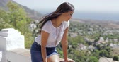sonhador : Pretty brunette in casual outfit looking excited while posing on viewpoint and exploring coastal city from height in summertime.